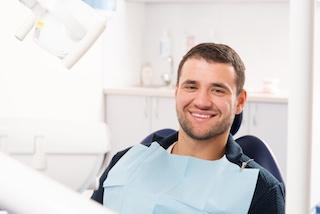man smiling in dental exam chair I dental insurance at woodin creek dental