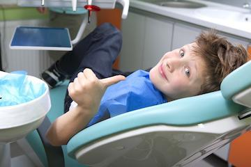 boy sitting in dental exam chair with thumbs up I Woodin Creek Dental