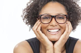 woman framing face with hands smiling brightly I dental crowns in woodinville wa