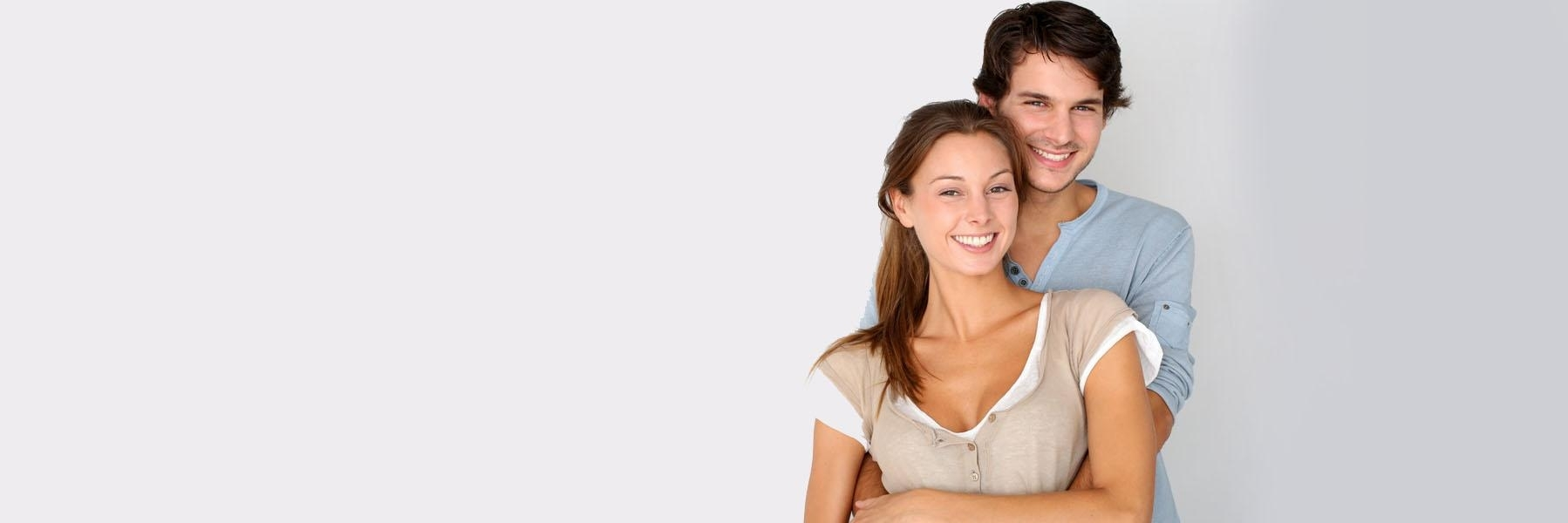Young couple hugging & smiling l Invisalign Woodinville WA