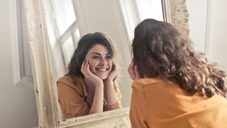 Woman Smiling in Mirror | Woodin Creek Dental