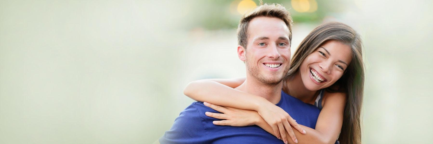 Young couple smiling & hugging outside l Invisalign 98011
